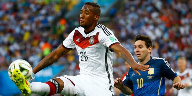 Germany's Jerome Boateng jumps to kick the ball in front of Argentina's Lionel Messi during their 2014...