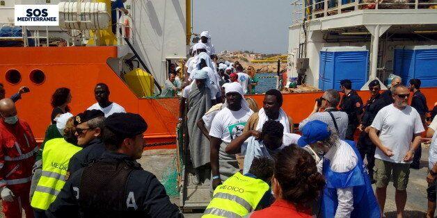 Migrants disembark from the SOS Mediterranee ship Aquarius at the Italian island of Lampedusa in this...