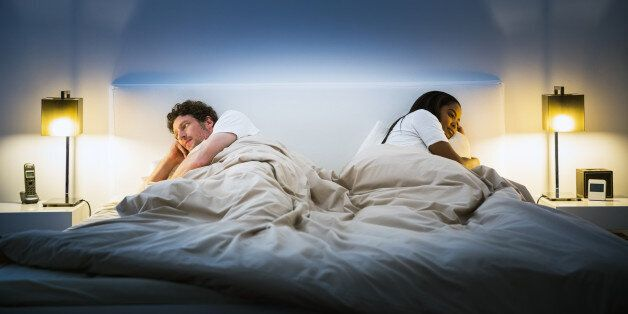 Multi-ethnic couple ignoring each other while lying in bed at