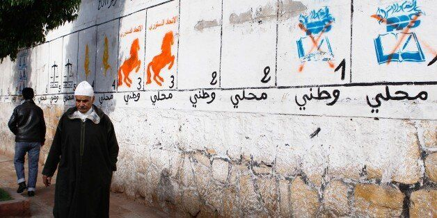 A man walks past electoral paintings representing political parties in Casablanca, Morocco, Thursday,...