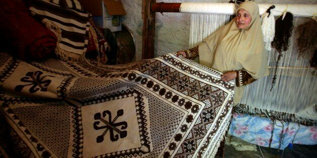 Nacera Benchenouf, 45, displays a carpet she made at her house in Babar village in the eastern city of...