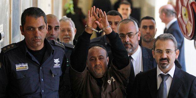 An Israeli prison guard escorts jailed Fatah leader Marwan Barghouti (C) to a deliberation at Jerusalem...