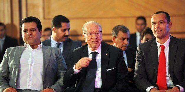 Tunisian former prime minister and presidential candidate, Beji Caid Essebsi looks on with the leader...