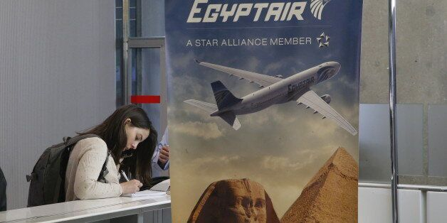 A reporter writes at the EgyptAir counter at Charles de Gaulle Airport outside of Paris, Thursday, May...