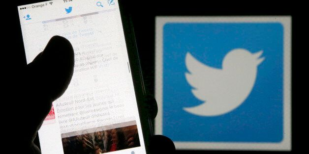 A man reads tweets on his phone in front of a displayed Twitter logo in Bordeaux, southwestern France,...
