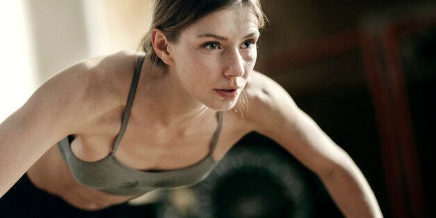 Close-up of focused female boxer doing push-ups in the
