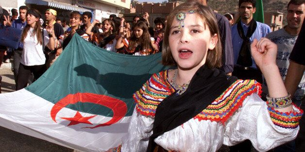 A young girl from the Kabylie region wears a traditional costume as sheholds the Algerian flag during...
