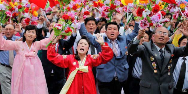 People react as they see North Korean leader Kim Jong Un during a mass rally and parade in the capital's...