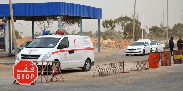 Tunisian security forces check vehicles near the Tunisian customs post at the Ras Jedir border crossing...