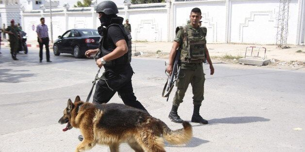 A Tunisian anti-terrorism brigade officer leads his dog after a shooting at the Bouchoucha military base...