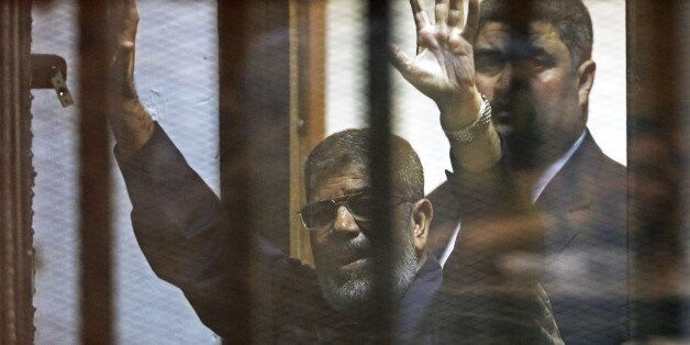 Deposed Egyptian President Mohamed Mursi greets his lawyers and people from behind bars after his verdict...