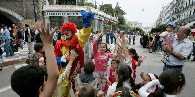 A clown performs with children at the main street of Didouch Mourad