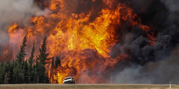 Smoke and flames from the wildfires erupt behind a car on the highway near Fort McMurray, Alberta, Canada,...