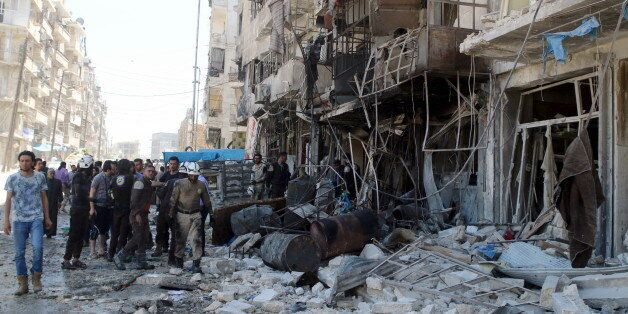 Residents and civil defence members inspect a damaged building after an airstrike on the rebel-held Tariq...