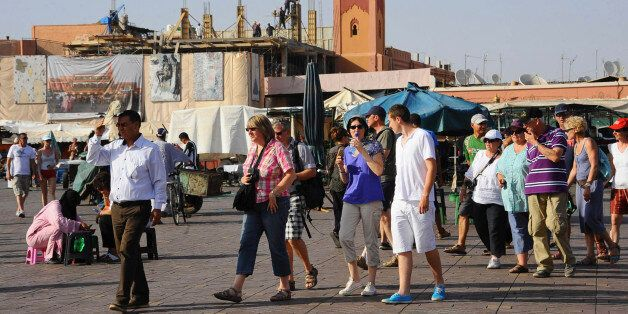 Tourists walk around the Argana restaurant (background) at Marrakesh?s famous Jemma el-Fnaa square, June...