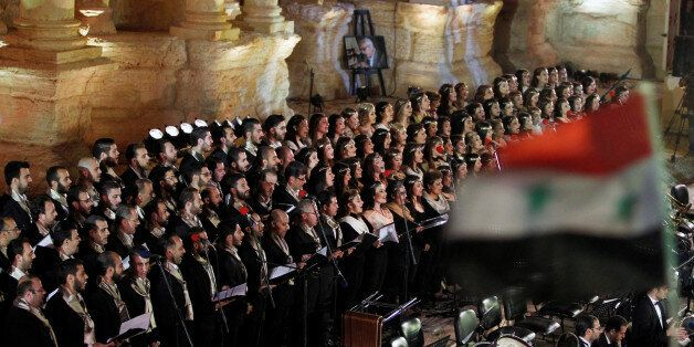 Al-Farah choir perform as a Syrian national flag flutters during a musical event