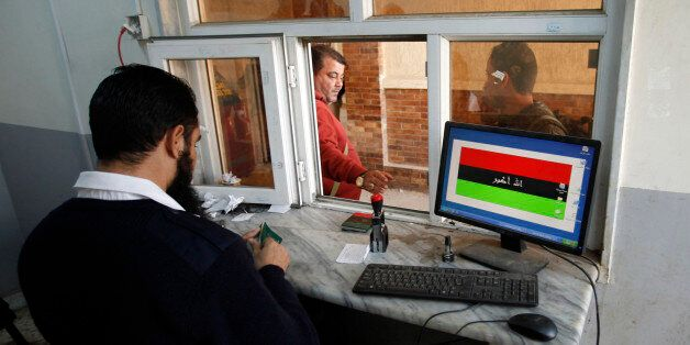 A border official checks passports at the Ras Jdir border, between Libya and Tunisia, 175 km west of...