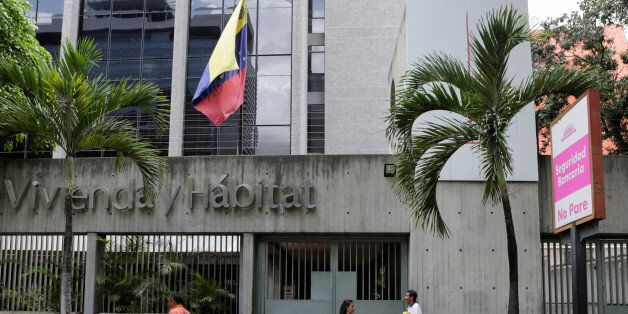 People walk past the closed entrance of the National Bank of Housing and Habitat building in Caracas,...