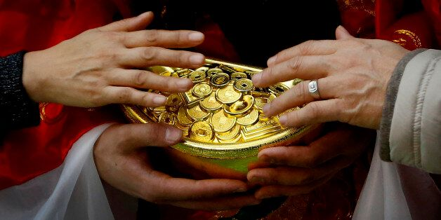 A man and a woman touch gold coins which are carried by a worker dressed as a God of Fortune at a shopping...