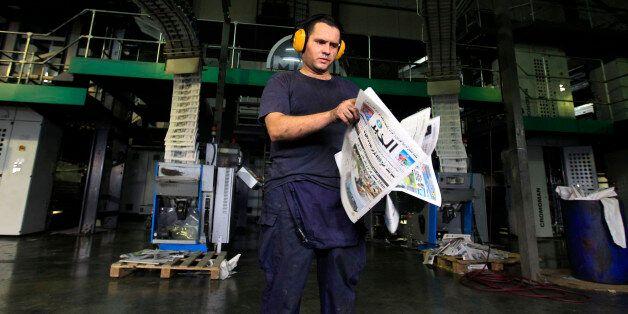A pressman checks newly printed Al Khabar newspapers for printing errors at the printing presses owned...