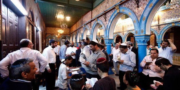 Jewish men pray inside the blue-tiled El Ghriba synagogue on the Tunisian island of Djerba following...