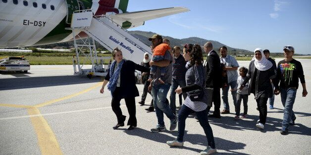 A group of Syrian refugees arrive to board a plane with Pope Francis at the airport of Mytilene, in the...