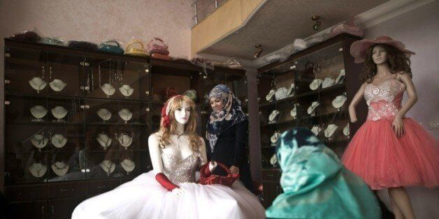 Une jeune Palestinienne regarde des robes de mariées dans une boutique à Gaza, le 5 avril