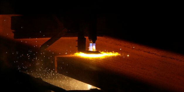 A red-hot iron slab is processed on a rolling mill of the ArcelorMittal steelworks in Ostrava, Czech...