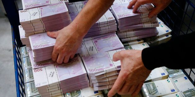 Wads of euro banknotes are stacked in a pile at the Money Service Austria company's headquarters in Vienna,...