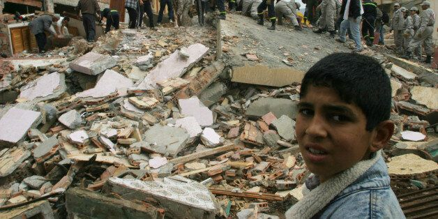 A BOY WATCHES RESCUE WORKERS TRYING TO LOCATE SURVIVORS UNDER RUBBLE OF DESTROYED BUILDING AFTER AFTERSHOCK...