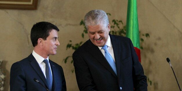 French Prime Minister Manuel Valls (L) speaks to Algerian Prime Minister Abdelmalek Sellal during a news...
