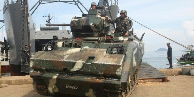Filipino soldiers aboard an armoured vehicle roll off from a Philippine Navy ship after arriving in Jolo,...
