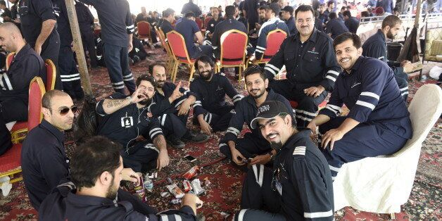 Kuwaiti oil sector employees sit in a shaded area on the first day of an official strike called by the...