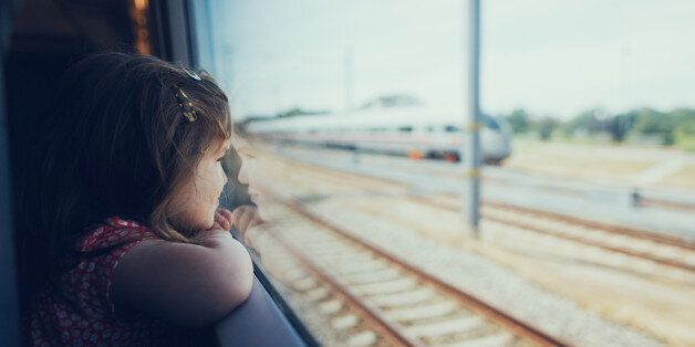 Young girl looking through the window in the train on the