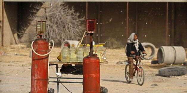 A man rides a bicycle as he passes tanks of gasoline in Kasserine, Tunisia January 30, 2016. A litre...