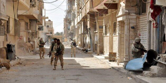 Forces loyal to Syria's President Bashar al-Assad walk with their weapons in Palmyra city after they...