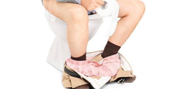 Studio shot of the legs of a man sitting on a toilet isolated on white