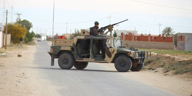 Tunisian soldiers ride an humvee as they search for attackers still at large in the outskirts of Ben...