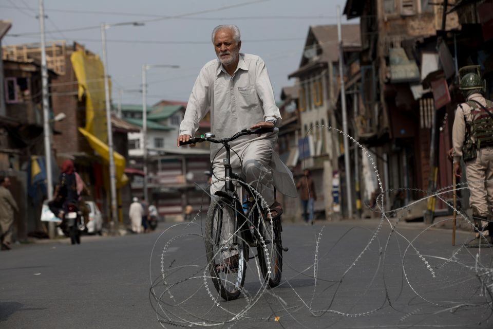 A Kashmiri cyclist rides past barbwire set up as road blockade in Srinagar on Sept.