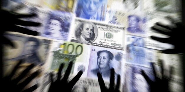Hands are silhouetted against a backdrop projected with the picture of various currencies of money in...