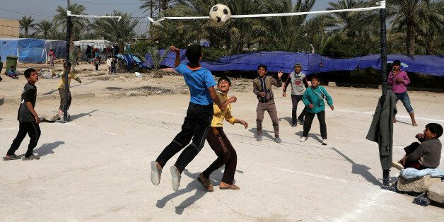 Teenagers who fled from Tikrit, Iraq, because they feared Islamic State militants play volleyball at...