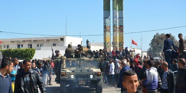 Tunisians wave to a military convoy during a visit of the prime minister in Ben Guerdane on March 13,...