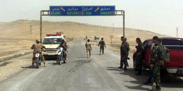 In this photo released by the Syrian official news agency SANA, Syrian government soldiers gather at...