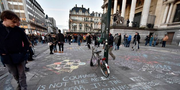 People write hundreds of messages on the asphalt at Place de la Bourse in the center of Brussels to mourn...