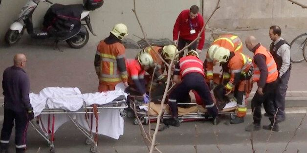 In this image made from video, emergency rescue workers stretcher an unidentified person at the site...
