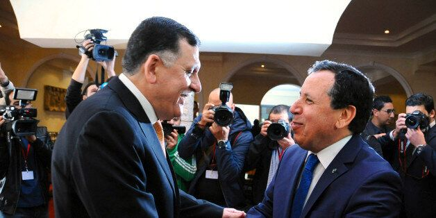 Tunisian Foreign Minister Khemaies Jhinaoui, right, shakes hands with Libyan prime minister Fayez Sarraj,...