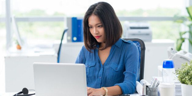 Concentrated businesswoman tying on laptop in