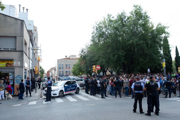 Mossos d'Esquadra controlan a la multitud que se ha congregado ante el domicilio en el que agentes de...