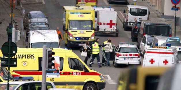 Emergency services evacuate a woman after a explosion in a main metro station in Brussels on Tuesday,...