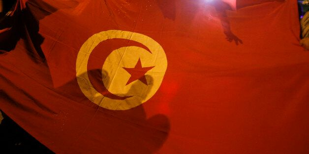 People carry a Tunisian flag during an protest against terrorism in Sousse, Tunisia, Saturday, June 27,...